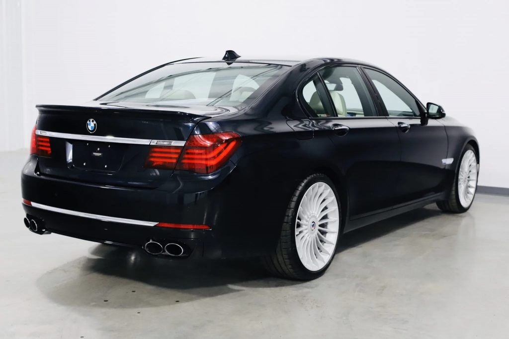 The rear 3/4 view of a dark-blue 2013 BMW Alpina B7 xDrive in a white warehouse