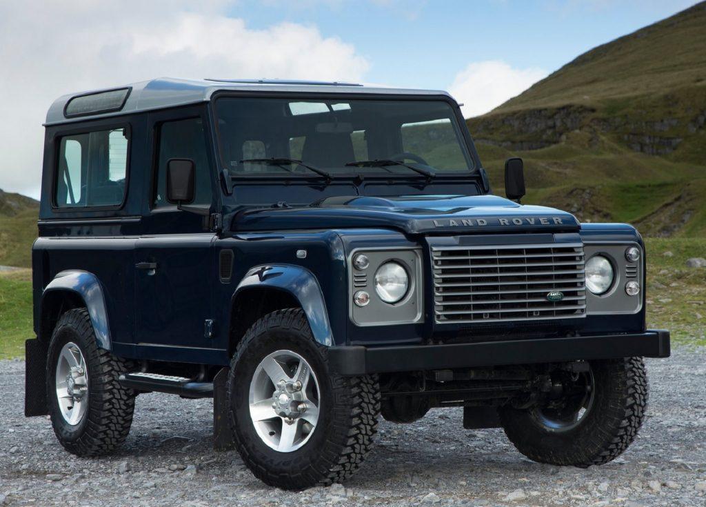 A dark-blue 2013 Land Rover Defender 90 among green hills