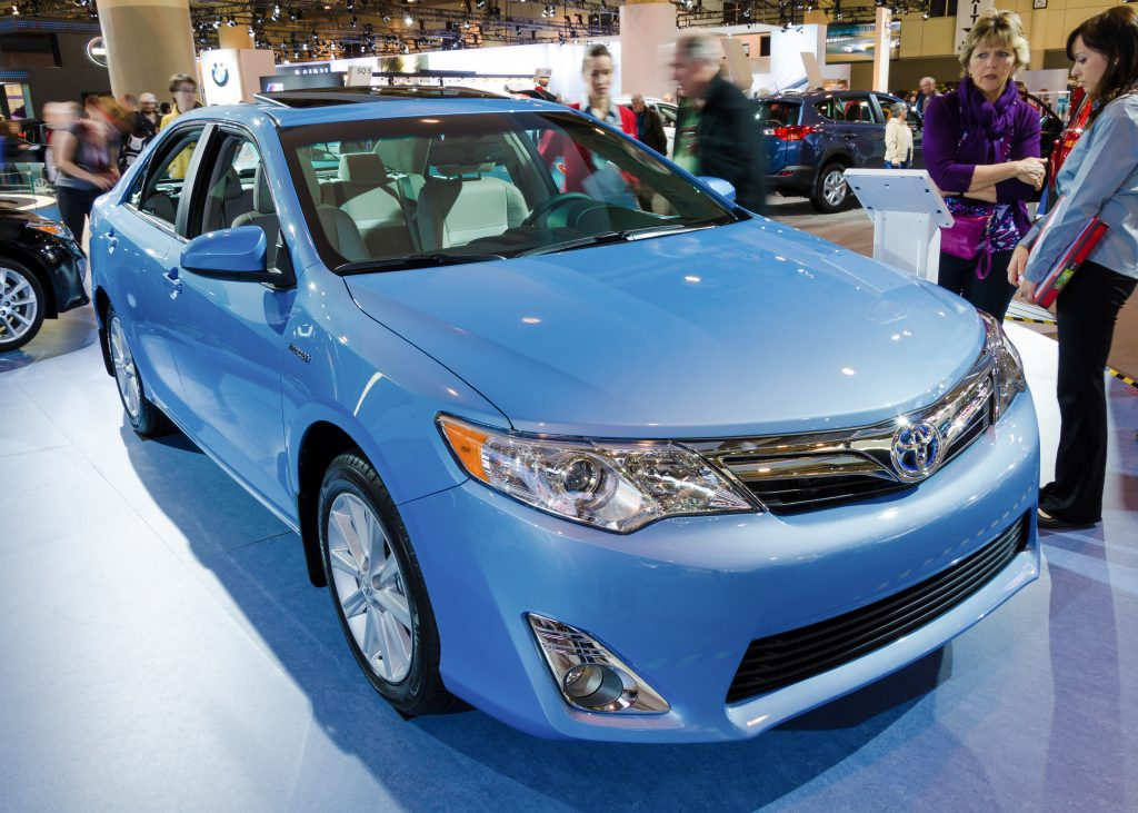 A light blue 2013 Toyota Camry XLE on display at an auto show