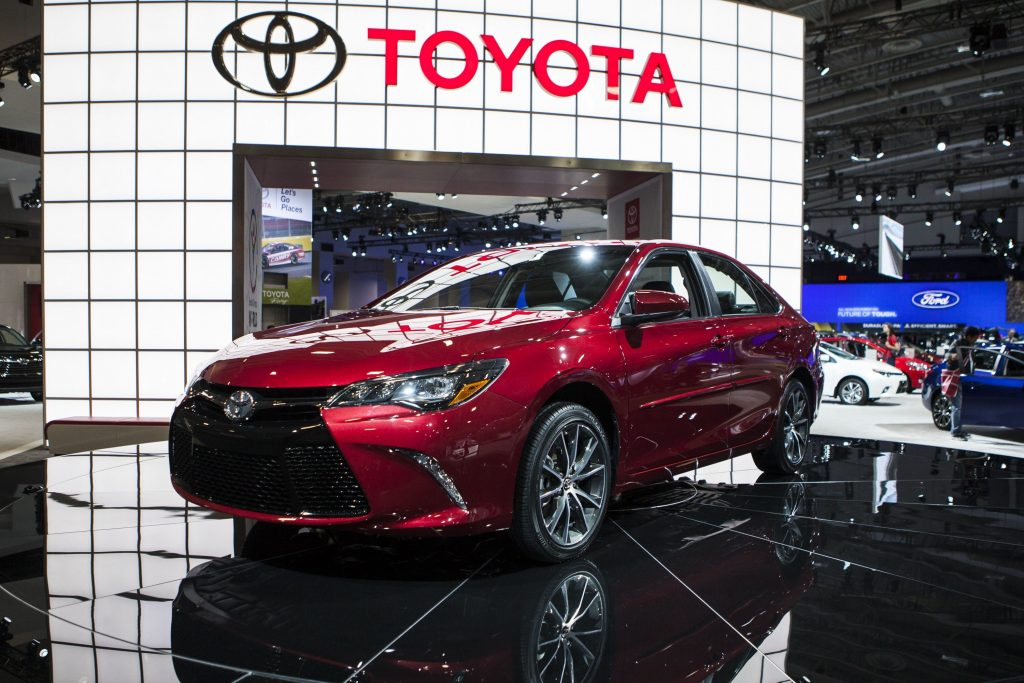 A red 2015 Toyota Camry on display at an auto show with Toyota in bold letters on the wall behind it.