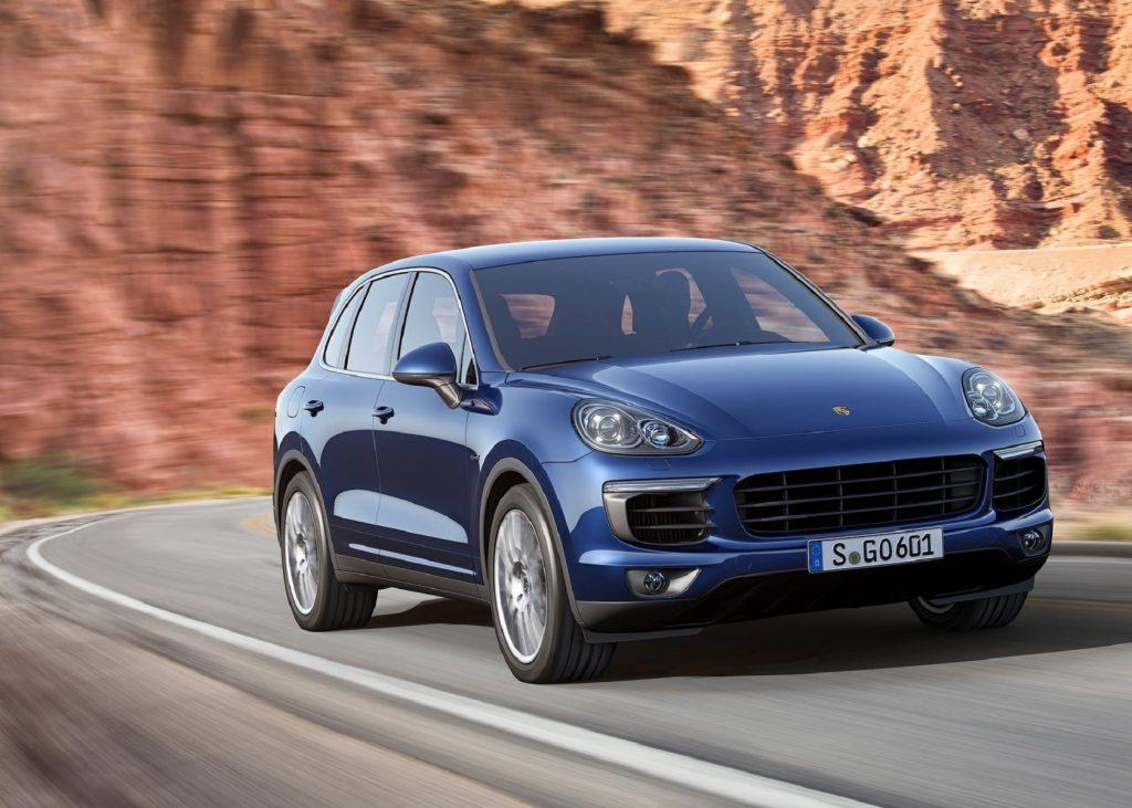 A blue 2016 Porsche Cayenne driving on a curving desert canyon road