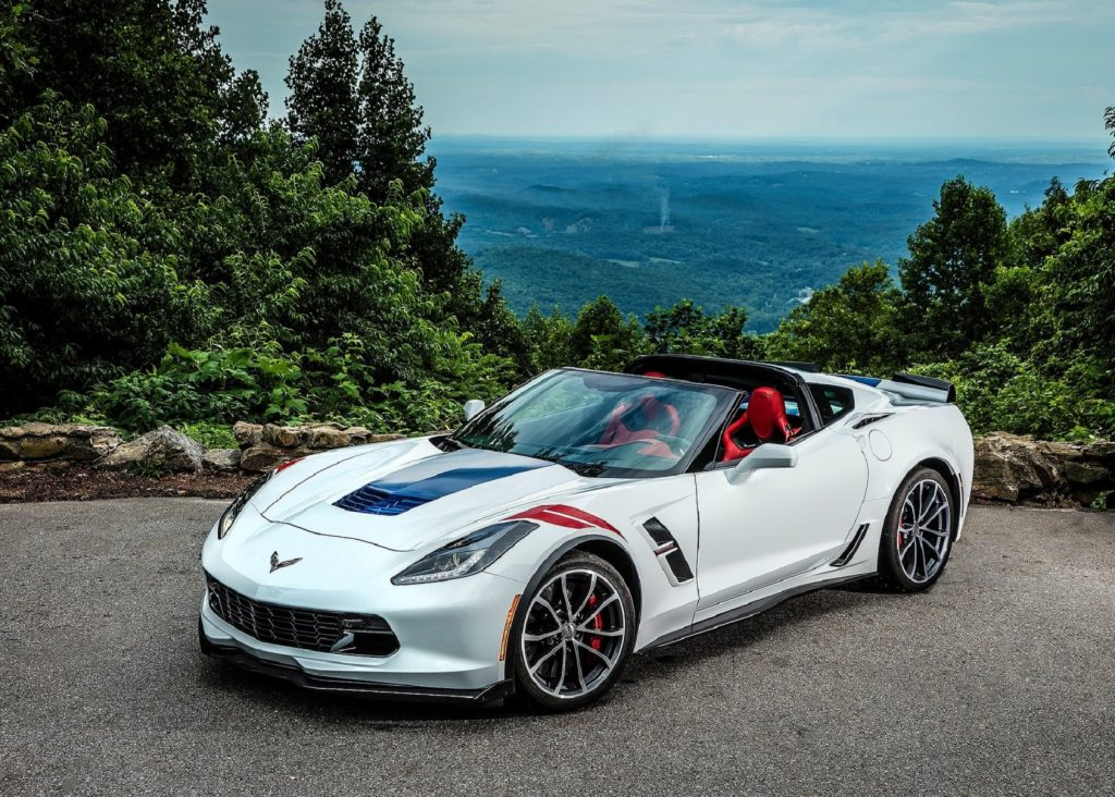 A white 2017 Chevrolet Corvette Grand Sport Convertible with red seats on a forested mountain road