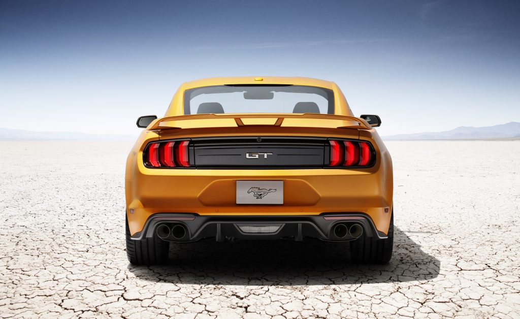 A look at the rear of an orange 2018 Ford Mustang and its iconic taillights