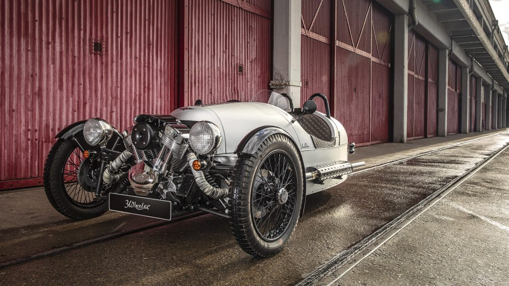 The front 3/4 view of a silver 2018 Morgan 3-Wheeler in front of a red barn