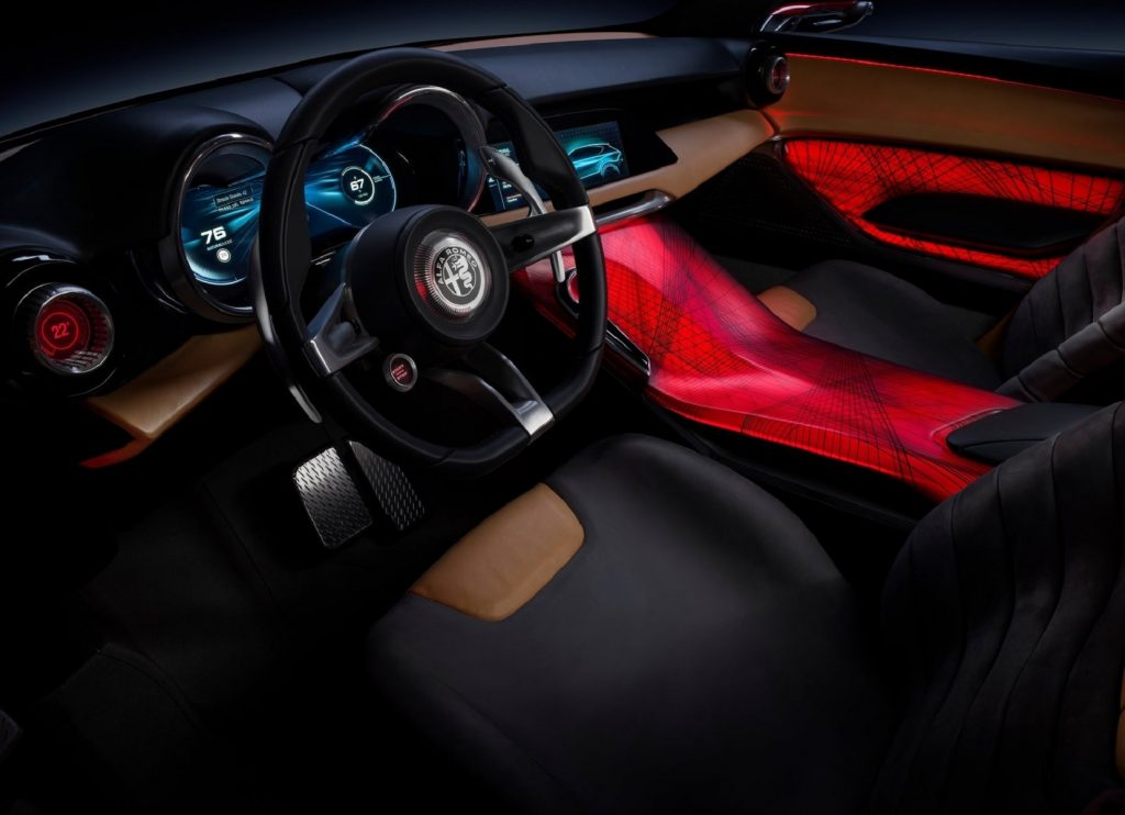 The red-lit center console and the tan-and-black-leather-upholstered front seats and dashboard of the 2019 Alfa Romeo Tonale Concept