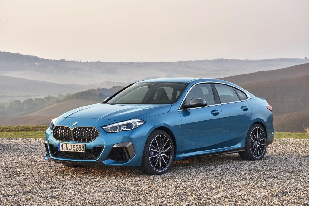 A blue 2019-2021 BMW 2 Series Gran Coupe sports car parked on display with a mountain range in the background