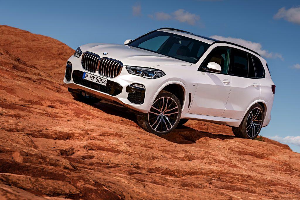 A white BMW X5 parked on rocky terrain