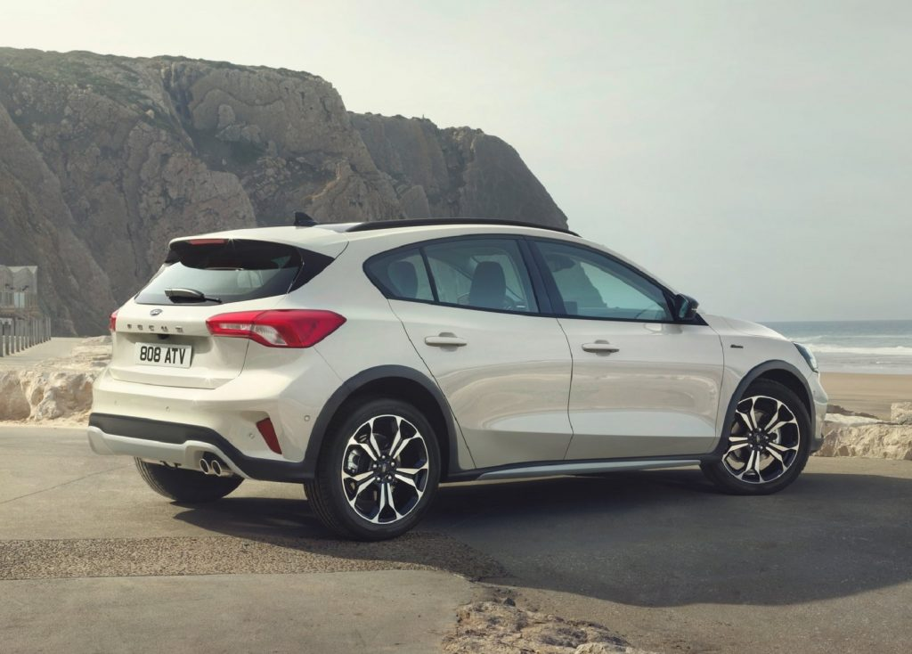 The rear 3/4 view of a white 2019 Ford Focus Active on a cliff-lined beach