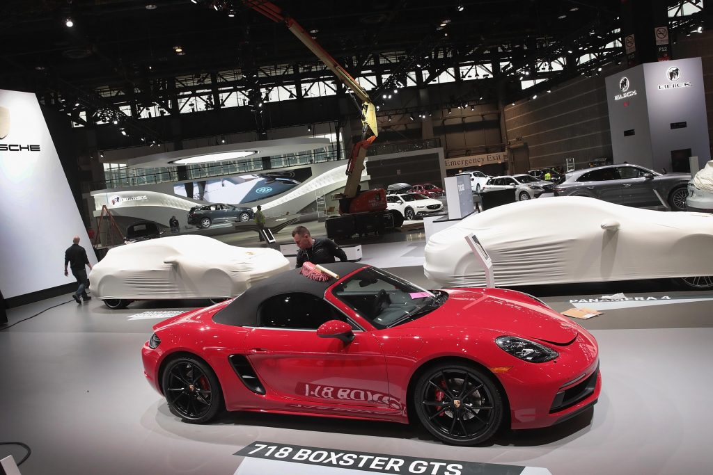 Workers prepare a red 20219-2021 Porsche 718 Boxster GTS sports car for the opening of the Chicago Auto Show