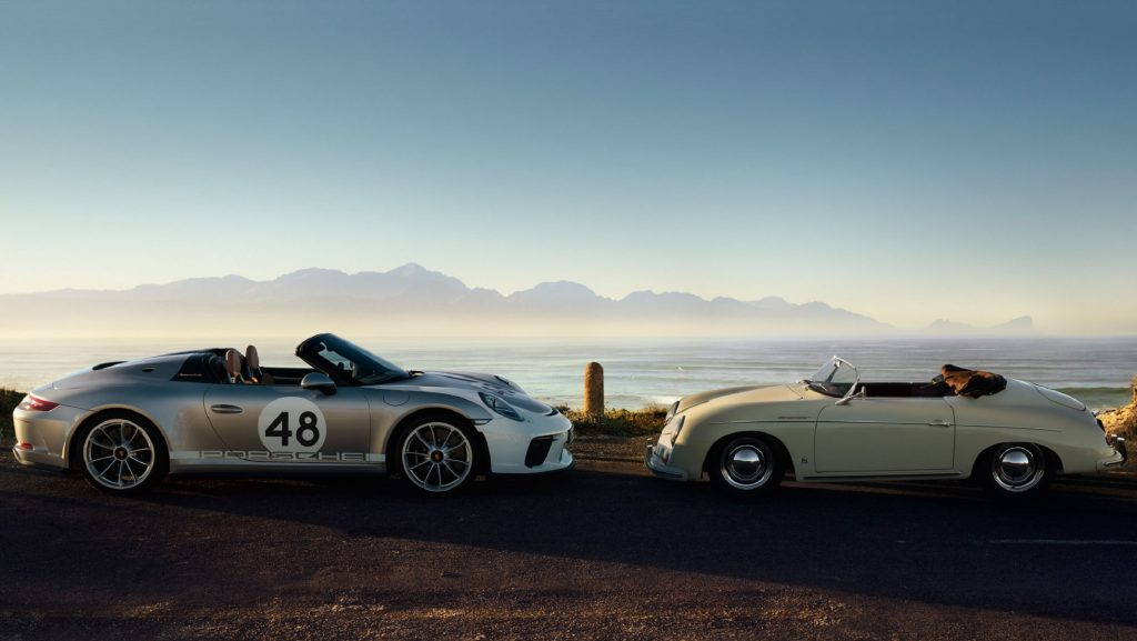 A white-and-silver 2019 Porsche 911 Speedster Heritage Edition next to a yellow 1954 Porsche 356 Speedster in front of the ocean