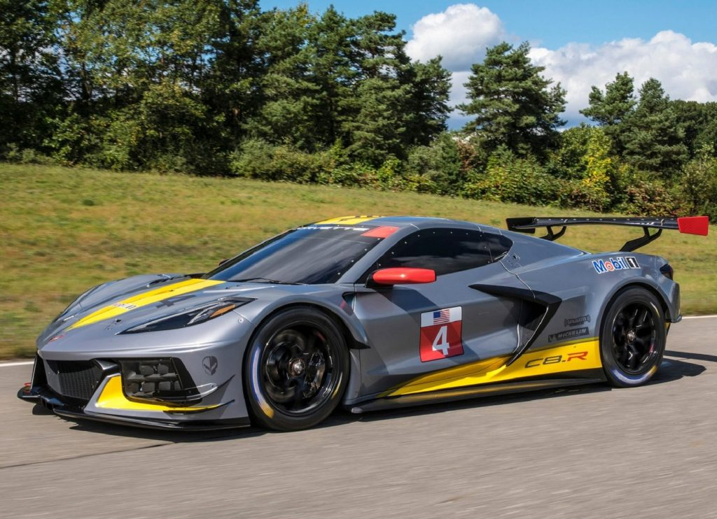 The gray-and-yellow 2020 Chevrolet Corvette C8.R drives down a forest-lined road
