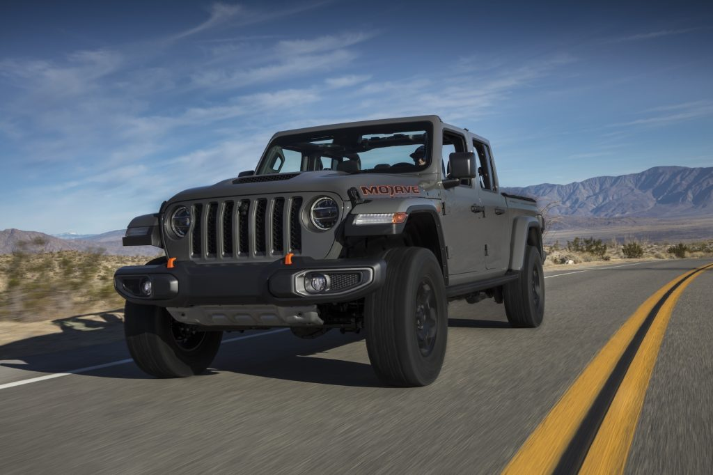 A gray 2020 Jeep Gladiator Mojave traveling on a two-lane highway in a mountainous desert