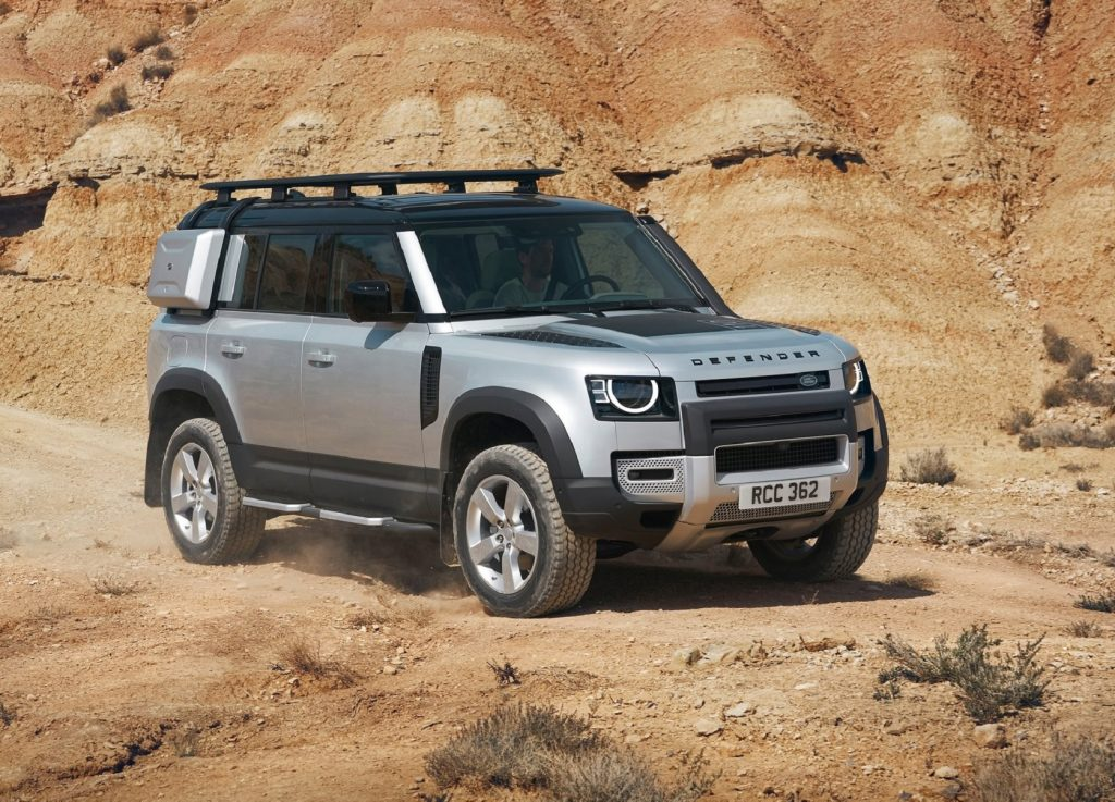 A silver 2020 Land Rover Defender 110 with exterior-mounted cases and a roof rack in the desert