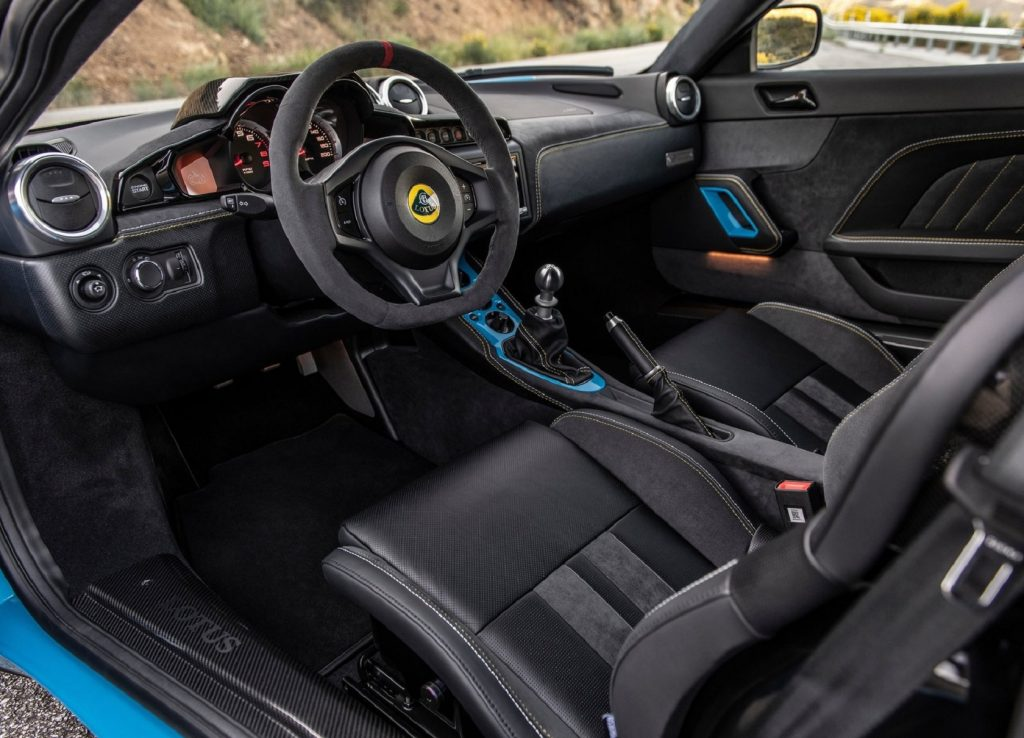 The black-leather-and-Alcantara-clad front seats and dashboard of a blue 2020 Lotus Evora GT