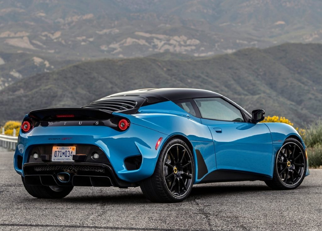 The rear 3/4 view of a blue 2020 Lotus Evora GT with the black slatted rear window on a mountain road