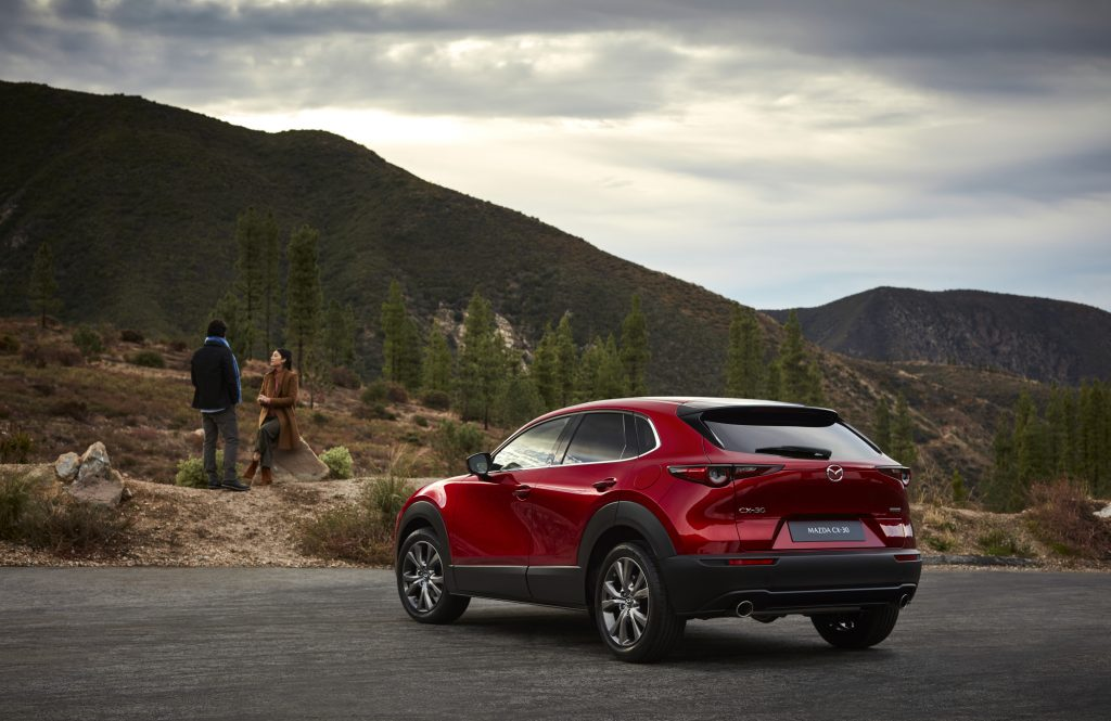 A red 2020 Mazda CX-30 parked, looking toward a mountain range
