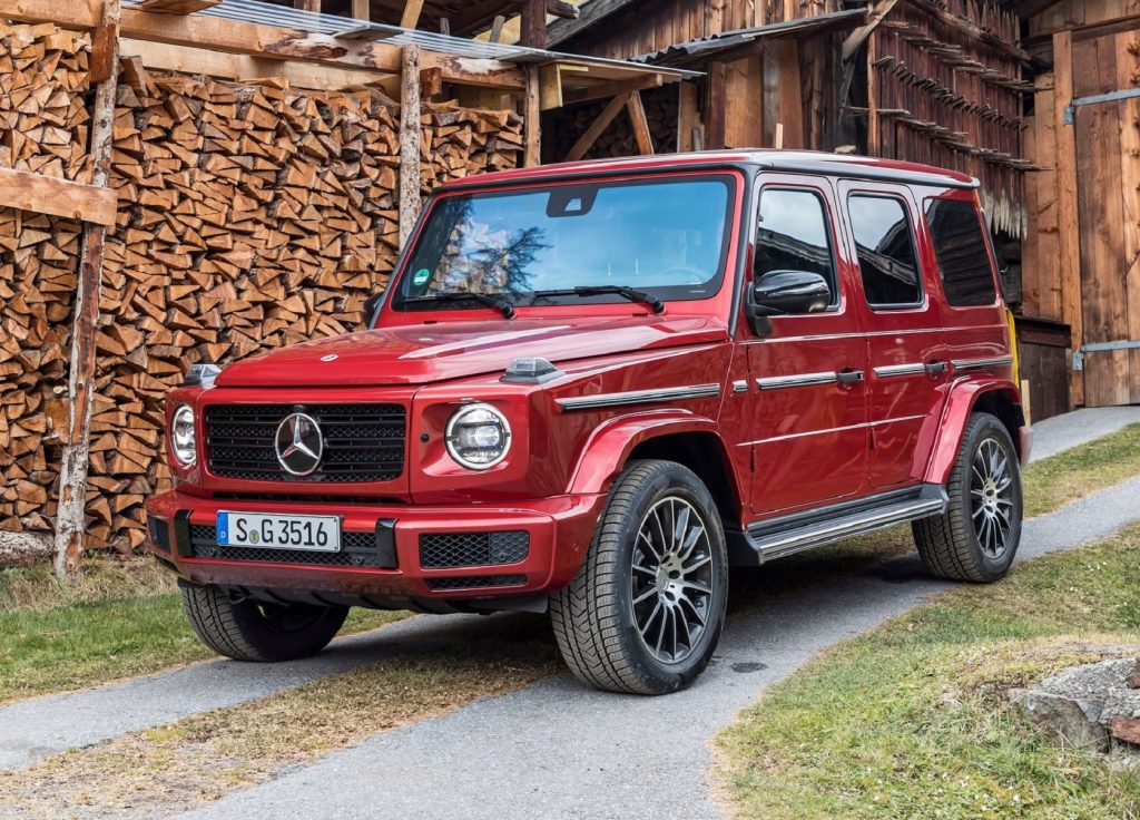 A red 2020 Mercedes-Benz G350d in front of an old wooden building