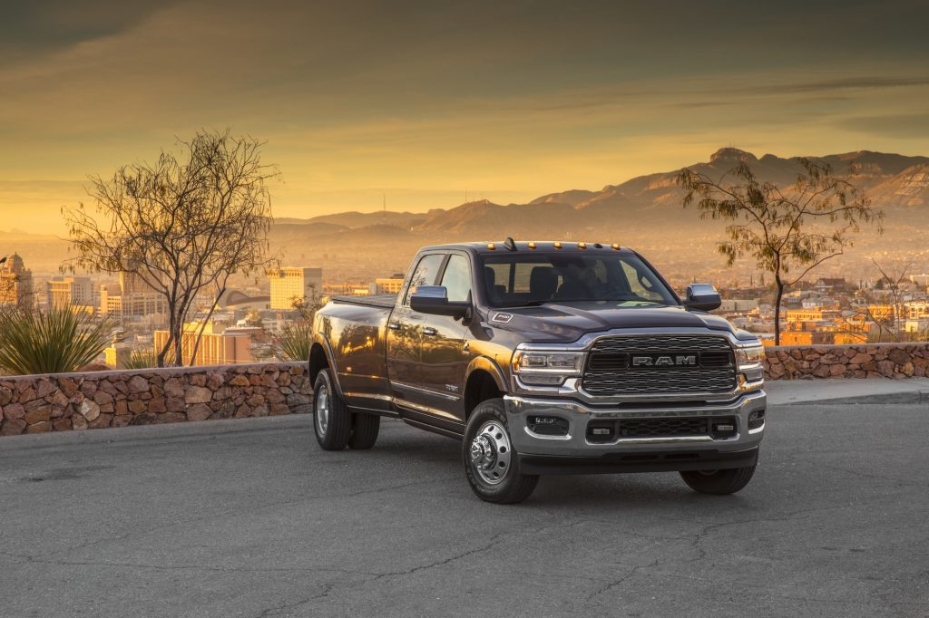 A dark 2020 Ram 3500 Heavy Duty Limited Crew Cab Dually pickup truck with a cityscape, mountains, and sunset in the background