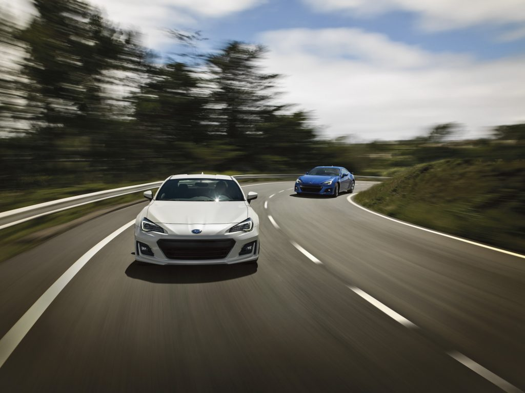 A white and a blue 2020 Subaru BRZ race on a winding two-lane highway flanked by hills and trees