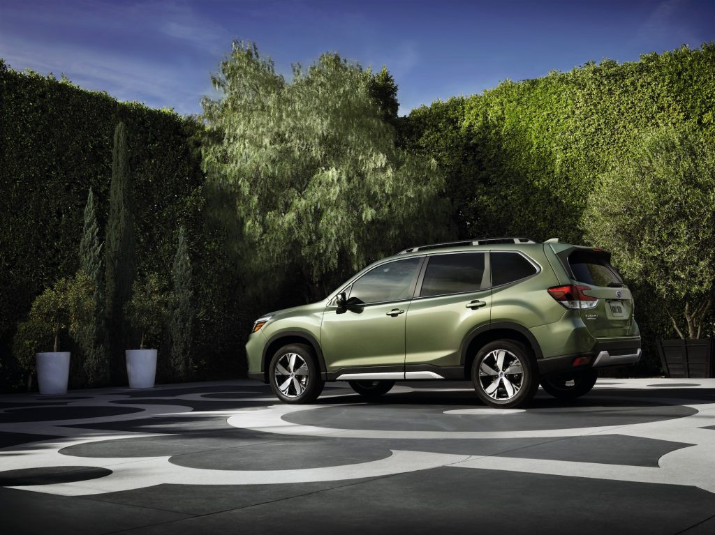 A green 2020 Subaru Forester parked on a patterned concrete slab surrounded by potted trees and shrubbery