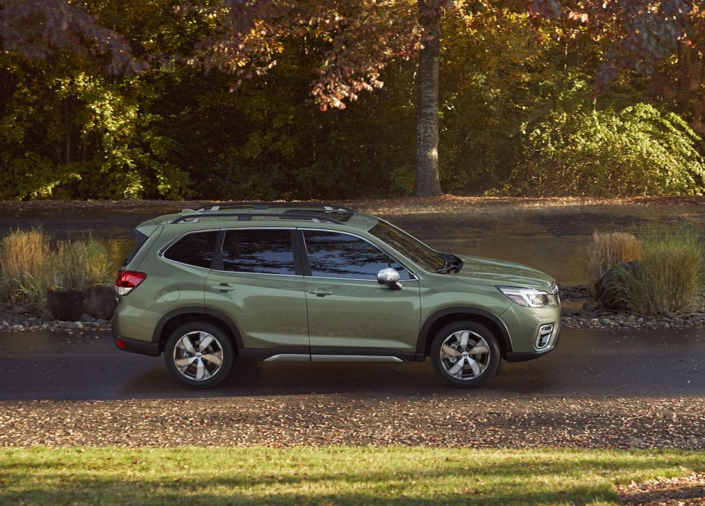 A green 2020 Subaru Forester compact crossover SUV parked on a sunny, tree-lined road