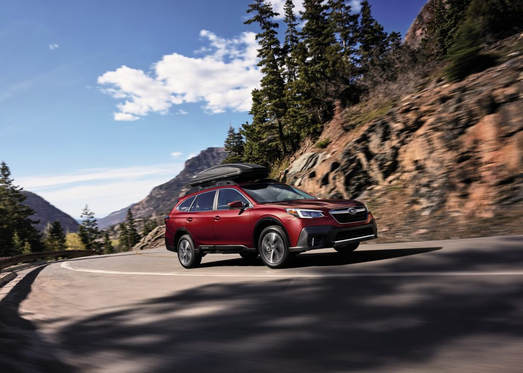 A red 2020 Subaru Outback driving down a highway road