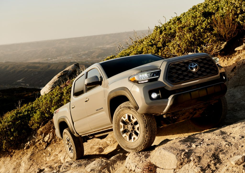 A gray 2020 Toyota Tacoma TRD Off-Road four-door pickup truck traversing rocky terrain on a mountainside