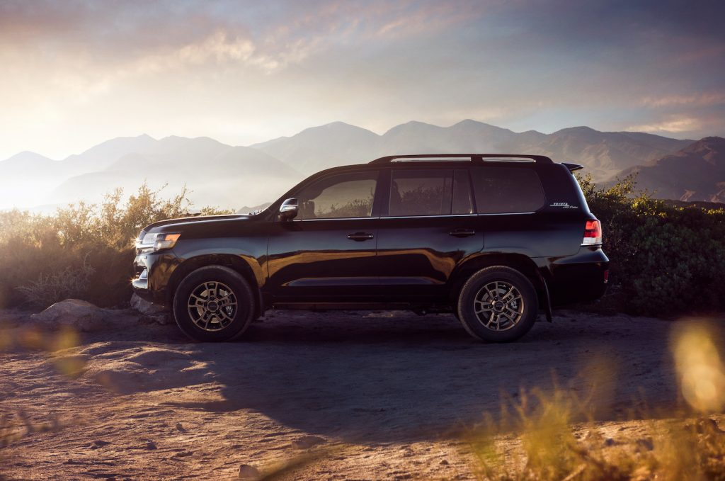 The Toyota Land Cruiser parked in front of a mountain range.