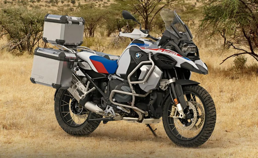A white-blue-and-red 2021 BMW R 1250 GS Adventure in the brush with accessory luggage