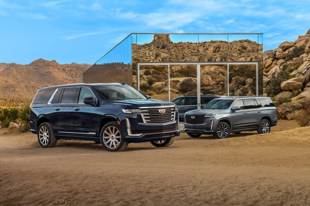 Two 2021 Cadillac Escalade ESV full-size SUVs parked in front of a small mirrored building in a mountainous desert