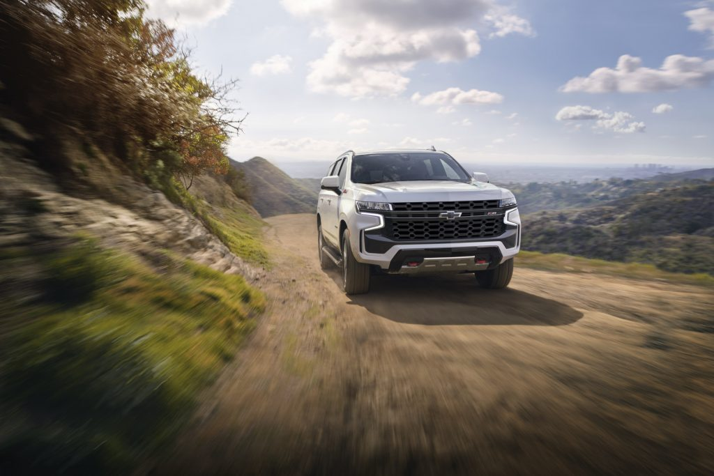 A front-facing look at a white 2021 Chevy Tahoe Z71 driving down a dirt road