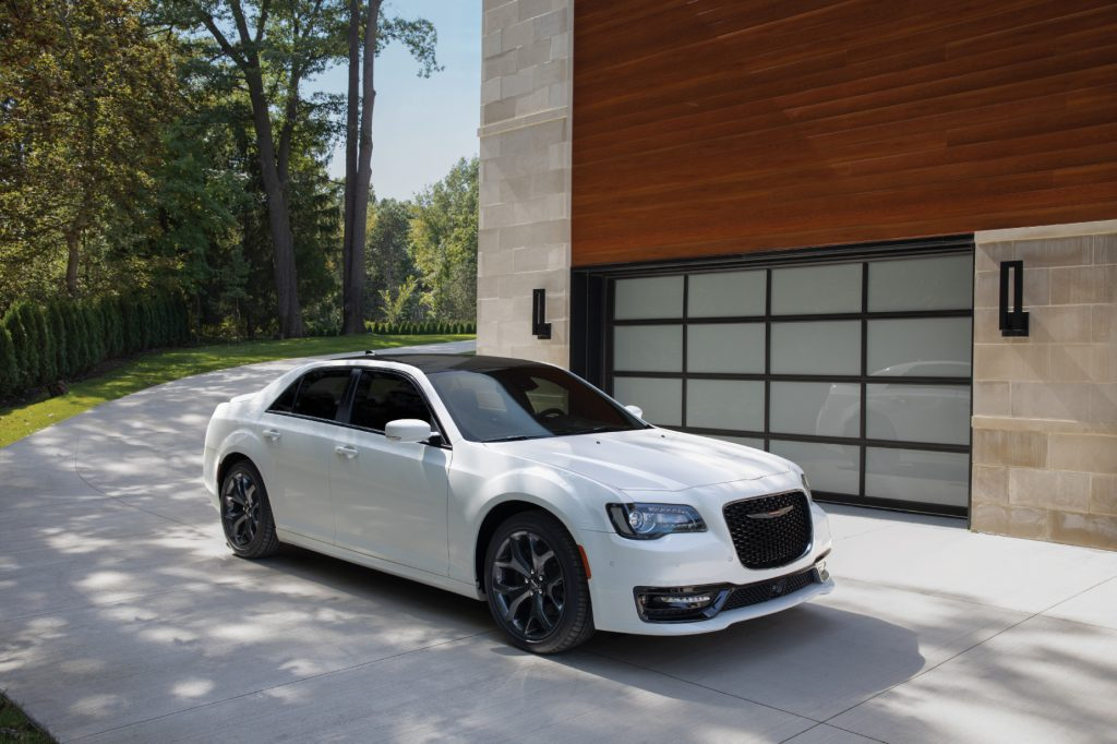 A white 2021 Chrysler 300 parked next to a building