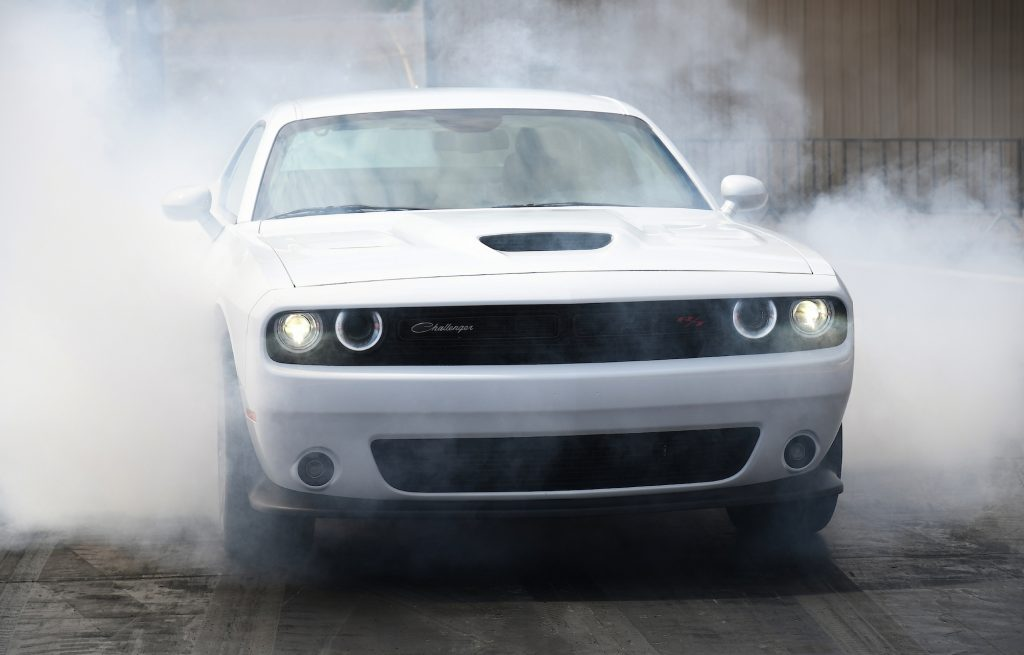 A white 2021 Dodge Challenger R/T Scat Pack 1320 does a burnout that creates smoke from the tires