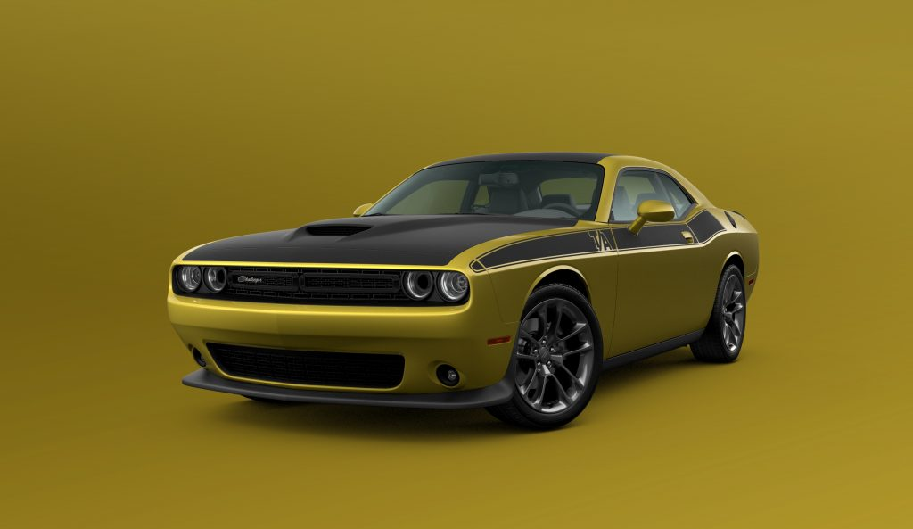 A gold and black 2021 Dodge Challenger T/A on display in front of a gold background