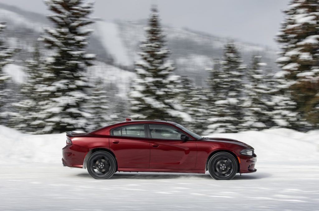 A red 2021 Dodge Charger GT AWD driving through the snow