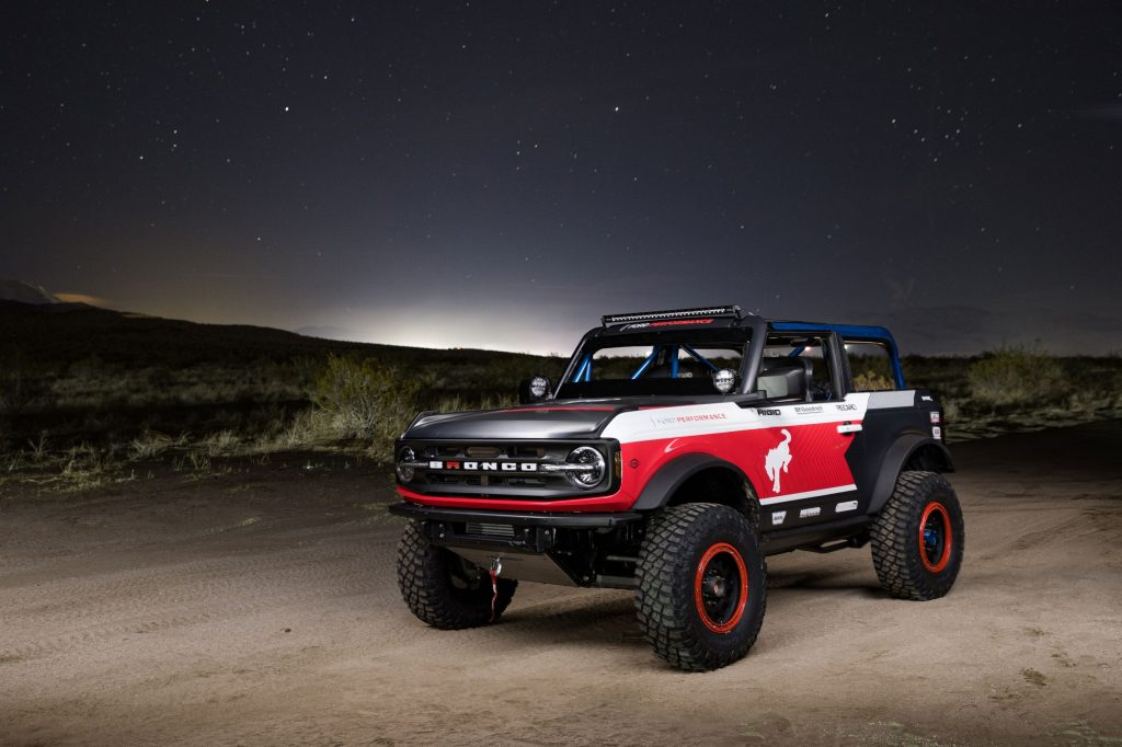 The red-white-and-blue 2021 Ford Bronco 4600 racer in the desert at night