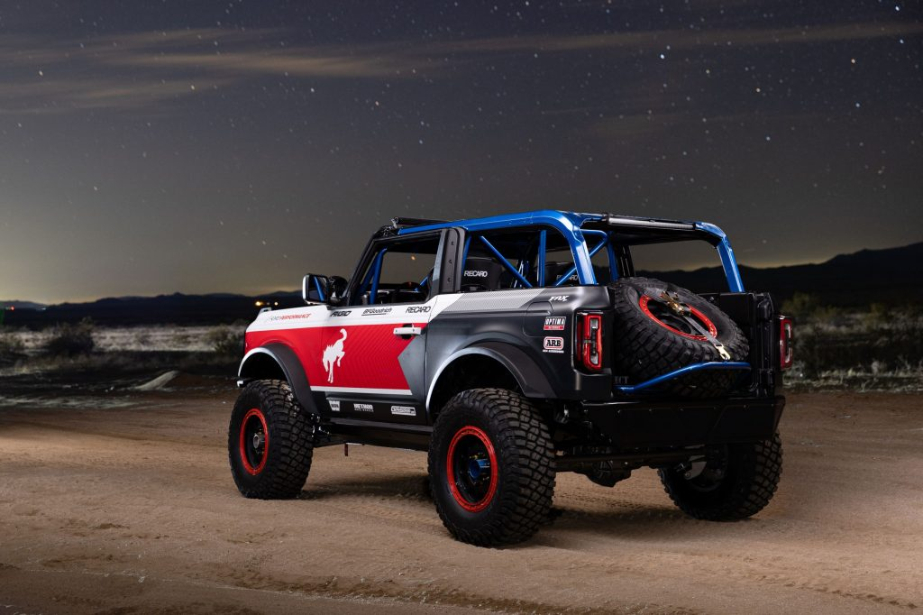 The rear 3/4 view of the red-white-and-blue 2021 Ford Bronco 4600 racer in the desert at night