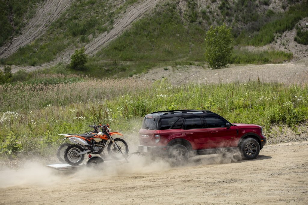 A red 2021 Ford Bronco Sport towing a pair of dirt bikes