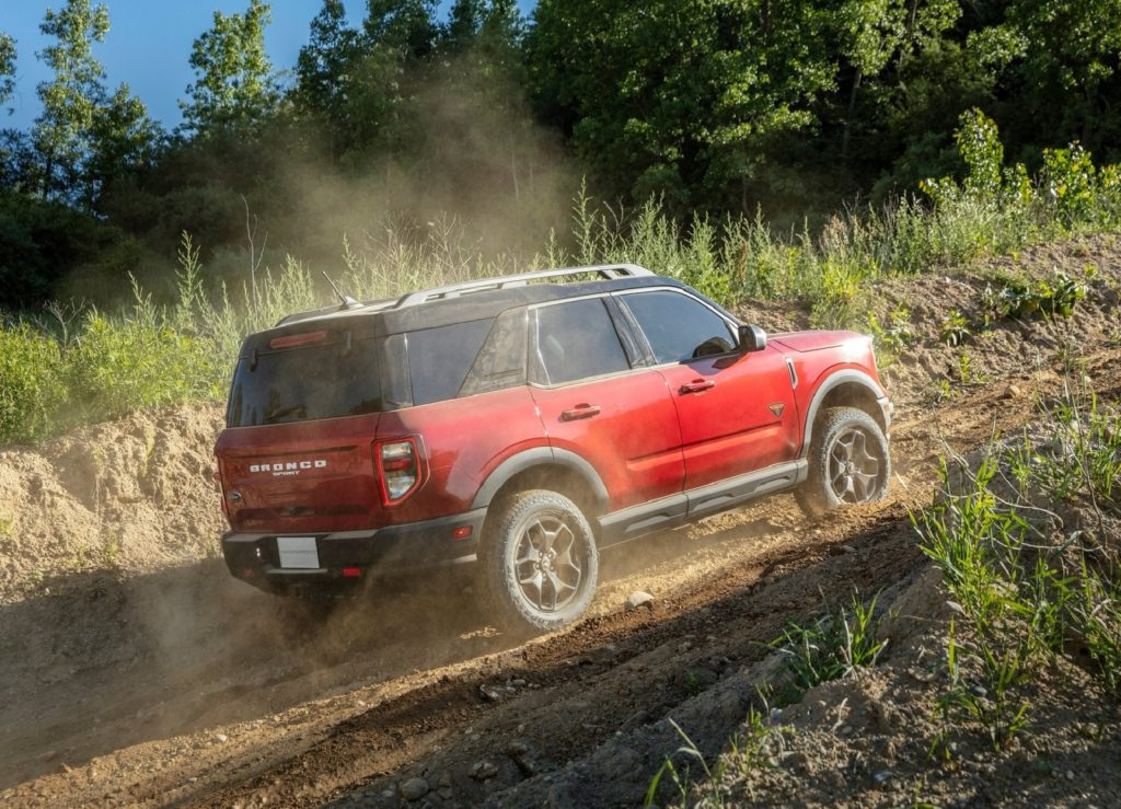 The rear 3/4 view of a red 2021 Ford Bronco Sport Badlands climbing a dusty off-road trail