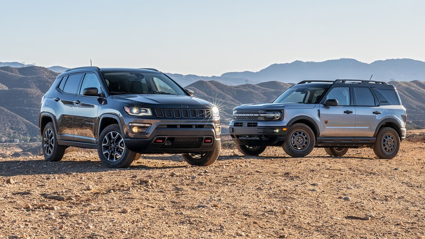A 2021 Jeep Compass and 2021 Ford Bronco parked in sand near each other