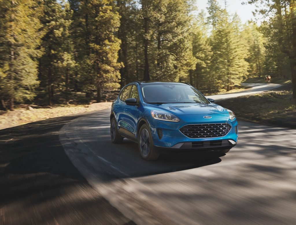 A blue 2021 Ford Escape compact SUV travels on a winding road through pine trees