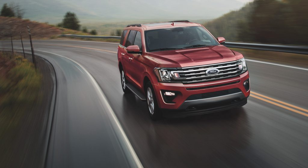 The 2021 Ford Expedition driving down an empty road.