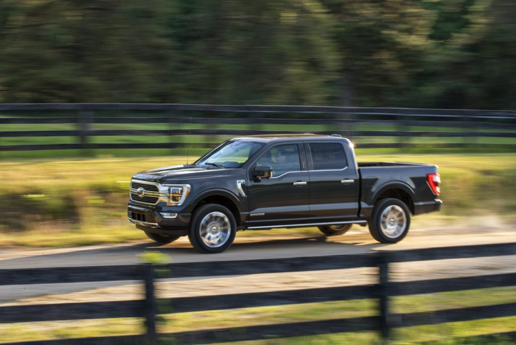 A dark-colored 2021 Ford F-150 travels on a rural dirt road flanked by wooden fencing