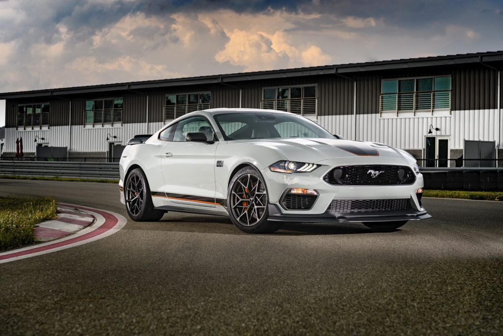 A white 2021 Ford Mustang taking a turn on a race track