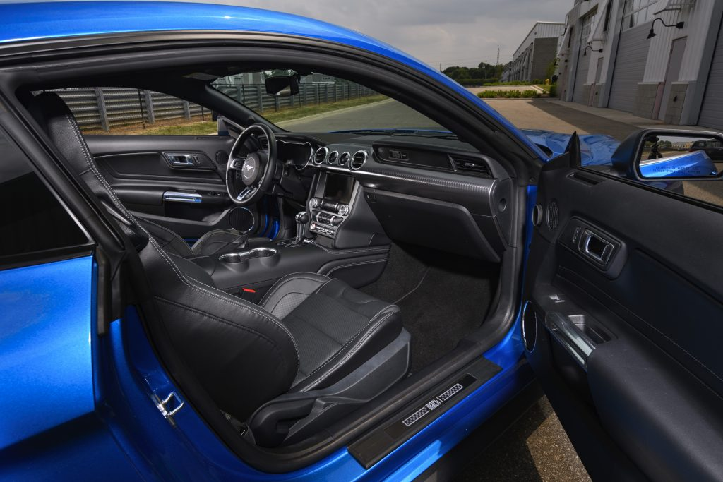 A look into the interior of a blue 2021 Ford Mustang from the passenger-side door.