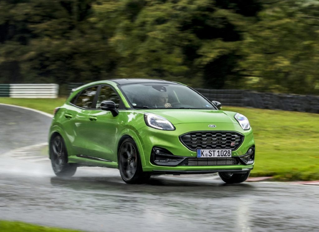 A green 2021 Ford Puma ST drives around a wet racetrack in the forest
