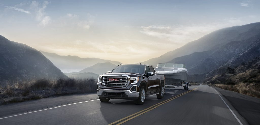 A black 2021 GMC Sierra SLT four-door pickup truck towing a boat on a two-lane highway in the mountains