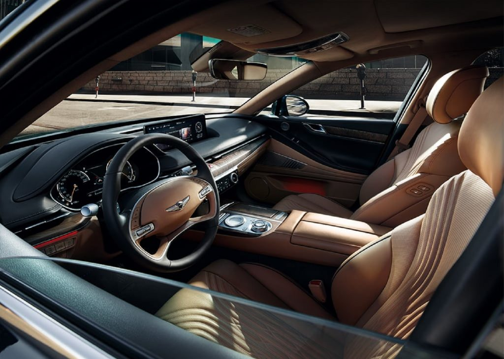 The tan-leather front seats and wood-trimmed dashboard of the 2021 Genesis G80