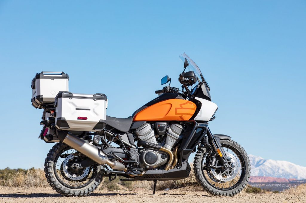 An orange 2021 Harley-Davidson Pan America 1250 Special in the desert equipped with accessory luggage cases