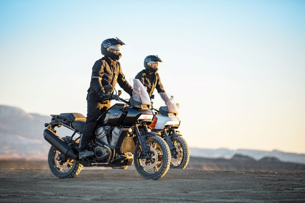 A rider on a black 2021 Harley-Davidson Pan America 1250 in front of an orange 1250 Special in the desert